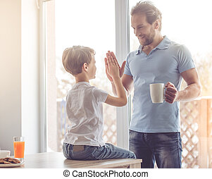 Father and son in kitchen - Father and son are giving high...