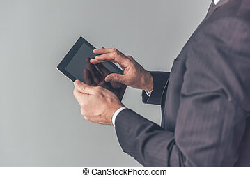 Handsome mature businessman with gadget - Cropped image of...