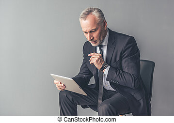 Handsome mature businessman with gadget - Handsome pensive...