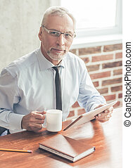 Handsome mature businessman in formal suit and glasses is...