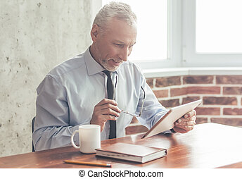 Handsome mature businessman in formal suit is using a...