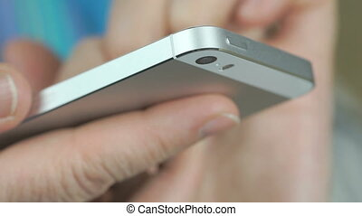 Woman enters text on silver cellphone indoors - Woman enters...