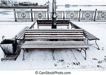 Frozen bench covered gritty rough hoarfrost on a cloudly...