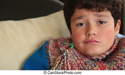 Child at home sick with flu, taking his temmperature - Tired...