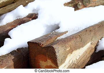 snow on wood beams in winter time