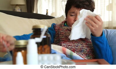 Sick,  tired child sneezing into tissue and resting