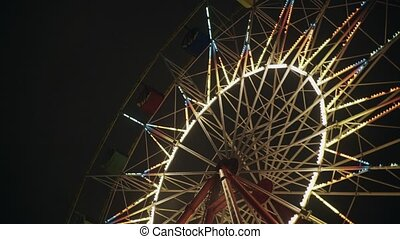 Park attraction ferris wheel carousel swing Night evening with illuminated light