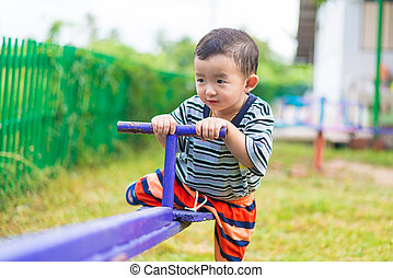 Asian kid riding seesaw board at the playground under...