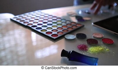Cosmetic products with sequin stars arranged on a background, makeup artist arranges cosmetics