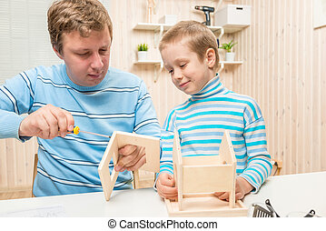 father shows his son how to build a bird feeder
