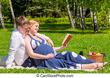 Future young parents reading the book on picnic for children