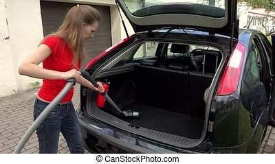 Woman Cleaning Boot Interior Of Car Using Vacuum Cleaner.