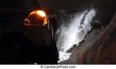 Car stuck in the snow. Paralyzed the movement of vehicles. Driver cleans the road from snow
