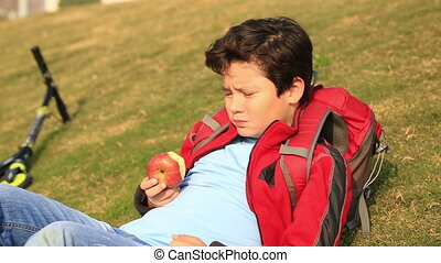 Portrait of a  young boy eating red apple at the outdoor