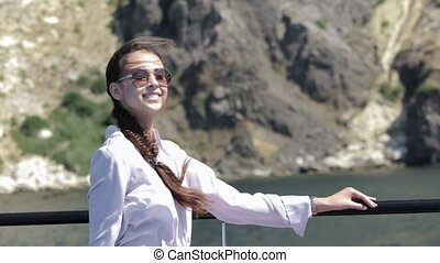 Smiling girl with the braid wearing sunglasses sitting on...