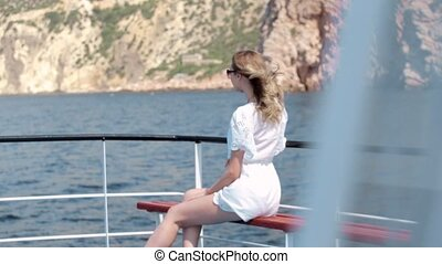 Elegant young woman on the cruise on the boat in the sea in...