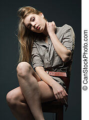 Seductive portrait of young woman sitting on chair -...