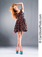 Beautiful red-haired girl on grey background