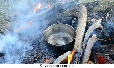 Warming up water in a metal saucepan on bonfire outdoors...