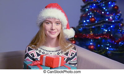 Woman in Santa hat with Xmas gift - Smiling female wearing...