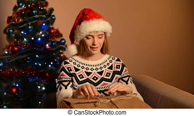 Woman in Santa hat unpacking Xmas gift - Woman wearing Santa...