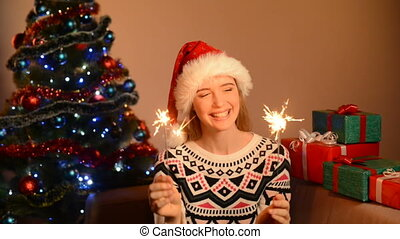 Woman in Santa hat with lighting sparklers - Beautiful happy...