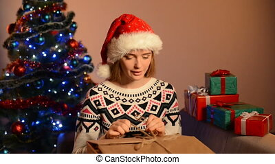 Woman in Santa hat unpacking Xmas gift - Beautiful happy...