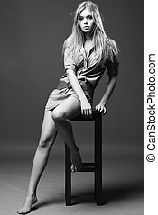 Black and white shot of girl sits on chair with naked legs