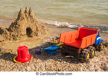 Sandcastle on the shore. Toy truck on sand. Turn on your...