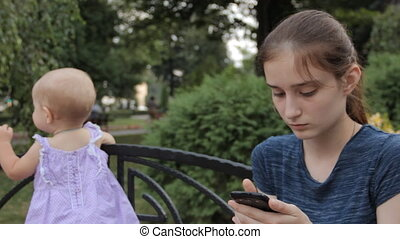 A very young nanny answering the smartphone and talking while the baby is standing next to her holding by the bench back.