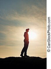 Silhouette human standing on rocky pedestal on nature...