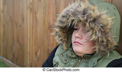 Winter portrait of cute boy in warm clothes coughing -...