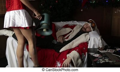 drunk santa claus lying on sofa, female nurse sexy woman in...