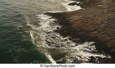 Aerial. Slow motion video of waves at sunset on a cliff....