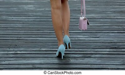 Amazing young woman in a short dress and blue high heels walking on wooden pier by the sea