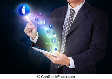 Businessman holding tablet with pressing usb flash drive...