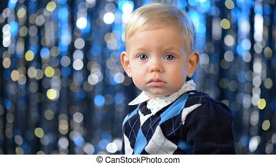 Smiling toddler child over blue holidays bokeh background -...