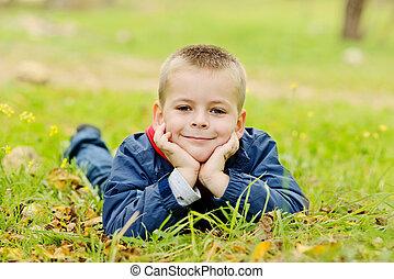 boy lying on the meadow - little boy lying on the meadow in...