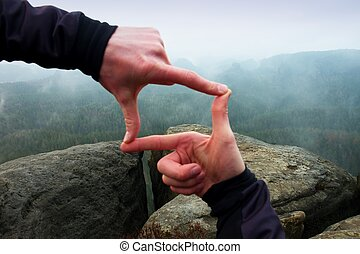 Close up of hands making frame gesture. Blue misty valley bellow rocky peak. Rainy spring day.