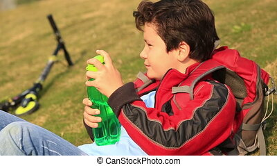 Young boy drinking water from a bottle - Portrait of a cute...