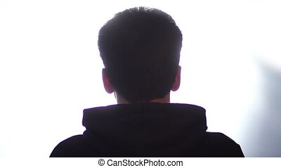 Back view of a man listening music with headphones - Back...