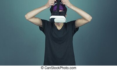 Young man with purple bangs using vr glasses headset doing...