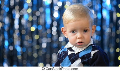 Adorable toddler child putting on the Santa hat over blue...