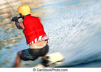Man on wakeskate doing tricks. Cable Wakeboard.