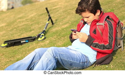 Young boy using smart phone the outdoor - Child with...