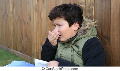 Young boy wipes his nose with a tissue Winter concept -...