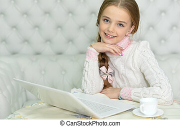 Preteen girl with laptop - Smiling preteen girl sitting at...