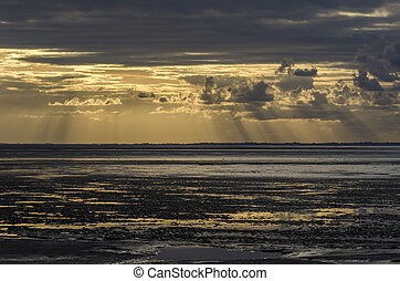 Sunset light through the clouds from the beach, Bay of Saint...