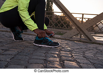 African american woman runner tightening shoe lace -...