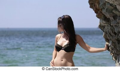 Charming brunette in black bikini standing next to the cliff...